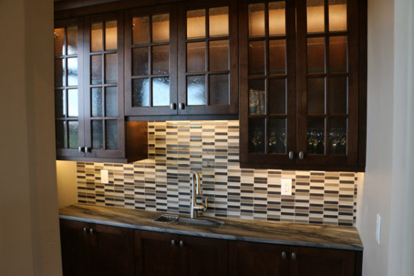Custom lighting features in and under cabinets in wet bar.